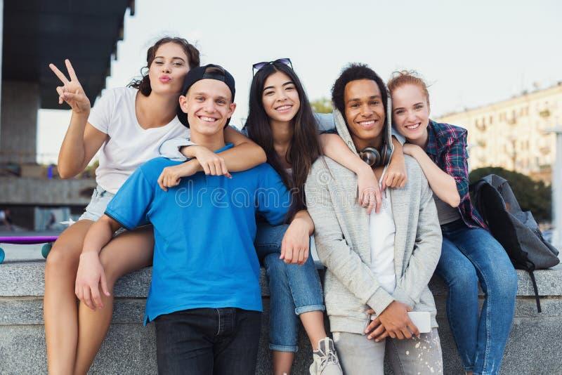 Szczęśliwi nastolatkowie spaja i śmia się przy kamerą zdjęcia stock
