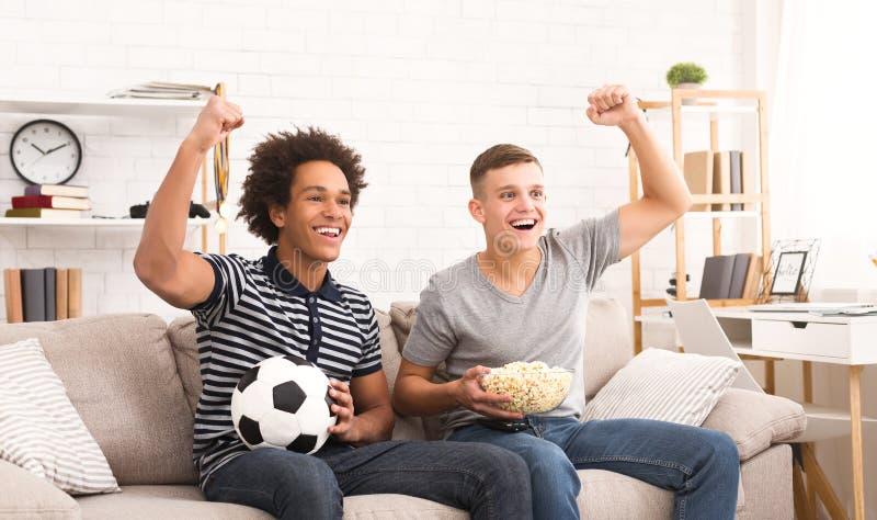 Szczęśliwi nastoletni fan piłki nożnej ogląda piłkę nożną na tv obraz royalty free