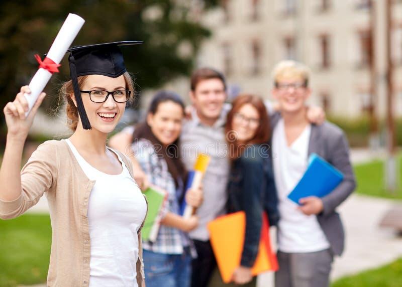 Szczęśliwi nastoletni ucznie z dyplomem i falcówkami fotografia stock