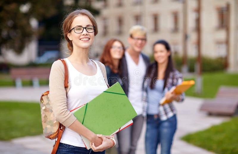 Szczęśliwi nastoletni ucznie z szkolnymi falcówkami fotografia stock