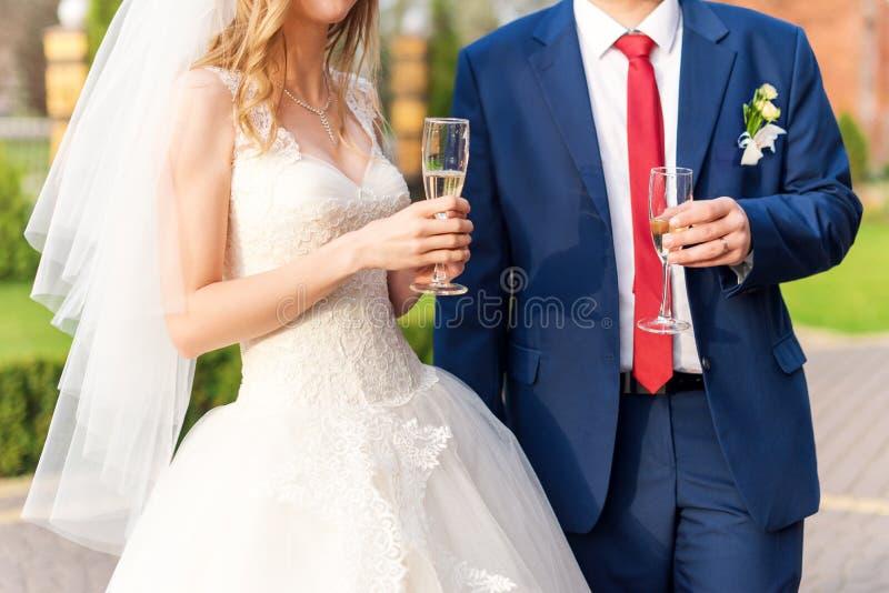 Szczęśliwi nowożeńcy dobierają się napoju białego ślubnego szampańskiego wino Ręki państwo młodzi z złotymi pierścionkami na pale obraz stock