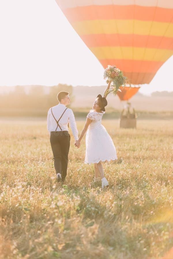 Szczęśliwi nowożeńcy są walkong w pogodnym polu blisko airballoon Tylny widok panna młoda utrzymuje up zdjęcia stock