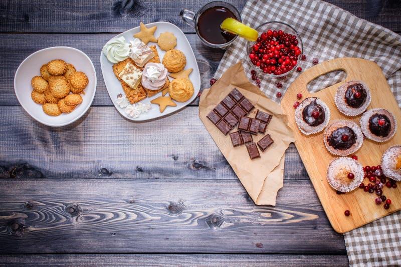 Szczęśliwi nowy rok cranberries, cukierki w deserowym talerzu, łamany czekoladowy bar na Kraft papierze i szkło herbata z cytryną obraz royalty free
