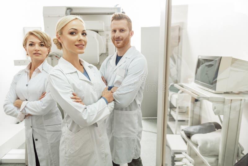Szczęśliwi ono uśmiecha się medyczni pracownicy wśród wyposażenia zdjęcia royalty free