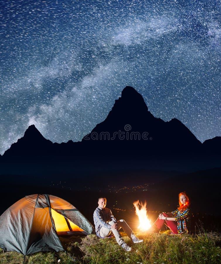 Szczęśliwi para turyści siedzi blisko ogniska i namiotu pod niesamowicie pięknym gwiaździstym niebem przy nocą długo ekspozycji zdjęcia royalty free