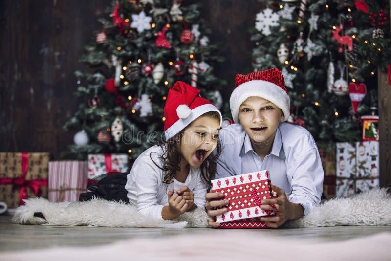 Szczęśliwi piękni dzieci chłopiec, dziewczyna z prezentami świętować wpólnie i zdjęcia royalty free