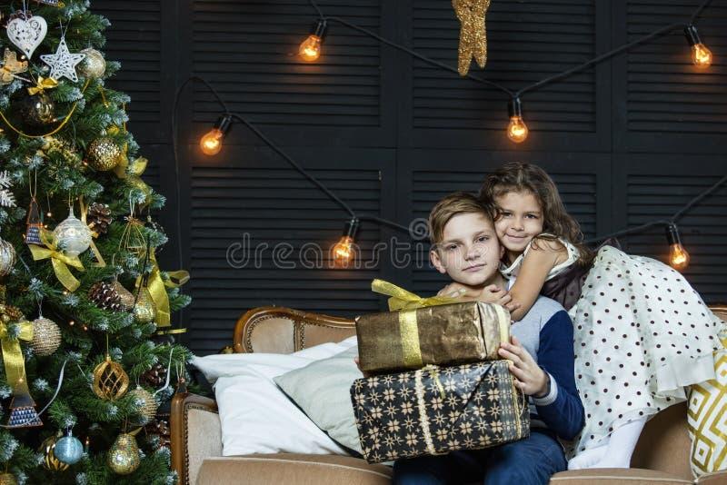 Szczęśliwi piękni dzieci chłopiec i dziewczyna z prezentami świętować Ch fotografia stock