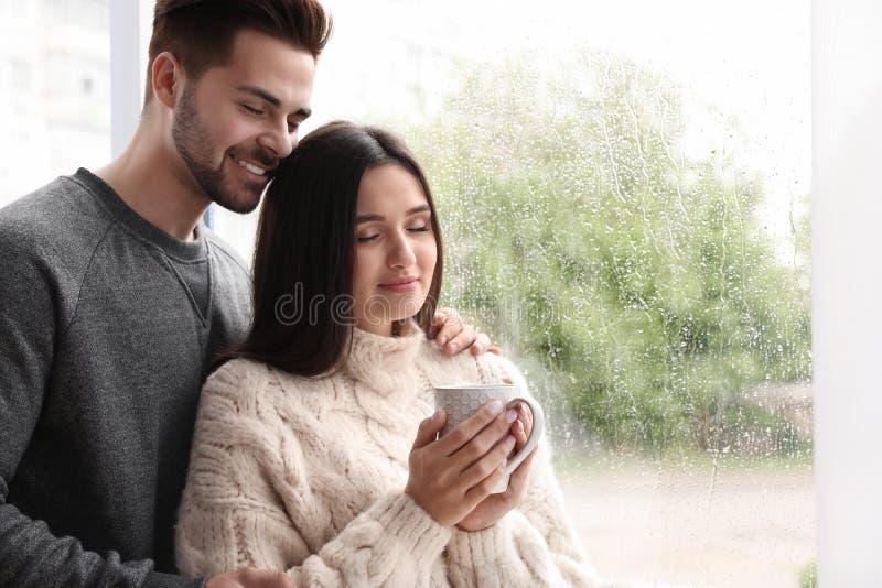 Szczęśliwi potomstwa dobierają się blisko okno indoors zdjęcia royalty free