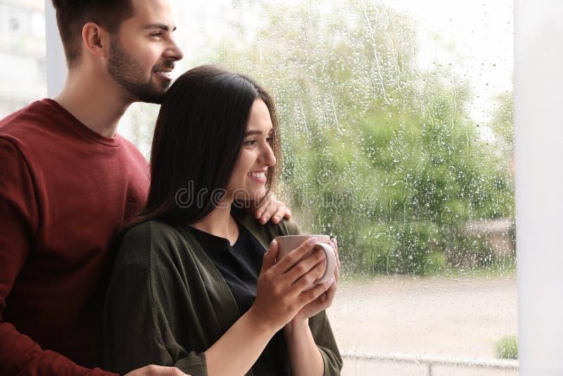 Szczęśliwi potomstwa dobierają się blisko okno na deszczowym dniu zdjęcie royalty free