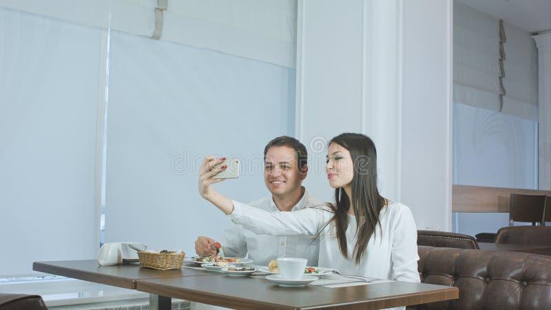 Szczęśliwi potomstwa dobierają się brać selfies z jedzeniem na smartphone przy restauracją obrazy stock