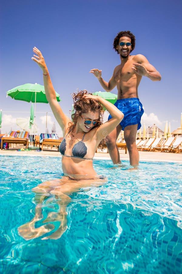 Szczęśliwi potomstwa dobierają się cieszyć się słonecznego dzień przy basenem obrazy royalty free