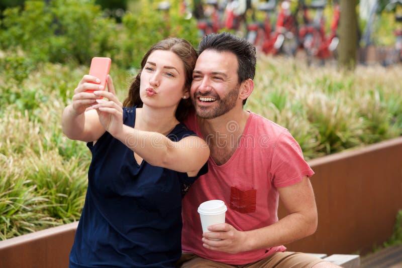 Szczęśliwi potomstwa dobierają się obsiadanie wpólnie bierze selfie na mądrze telefonie fotografia stock