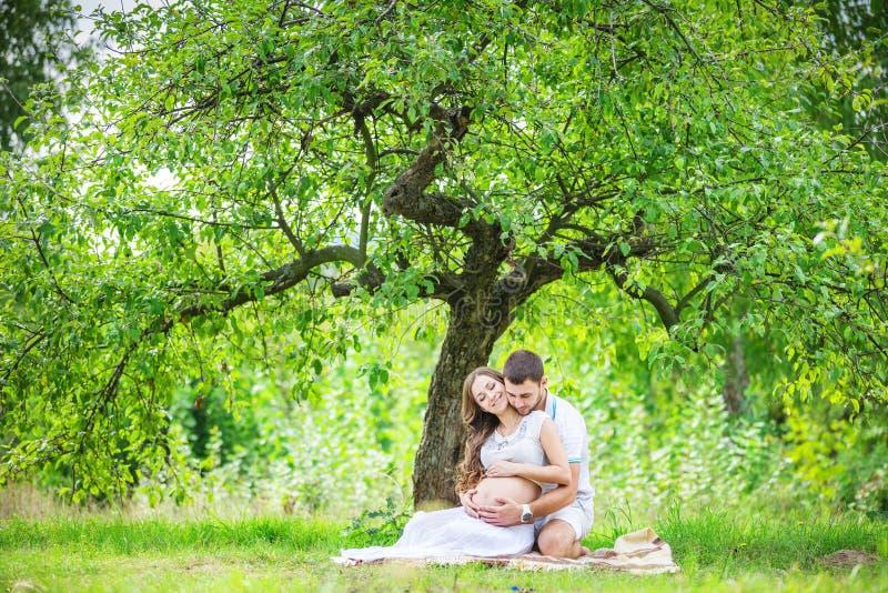 Szczęśliwi potomstwa dobierają się oczekiwać dziecka, kobieta w ciąży z męża wzruszającym brzuchem fotografia royalty free