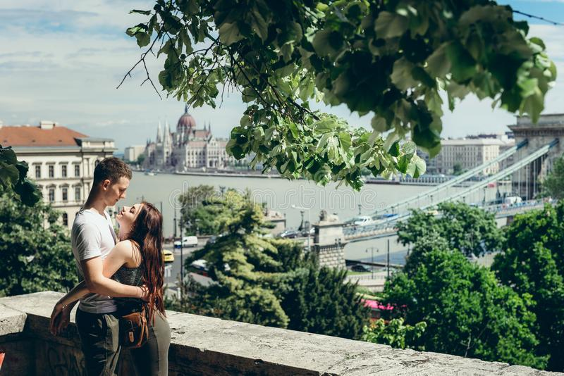 Szczęśliwi potomstwa dobierają się w miłości delikatnie ściskają na balkonie przy tłem Budapest panorama w Węgry obraz royalty free