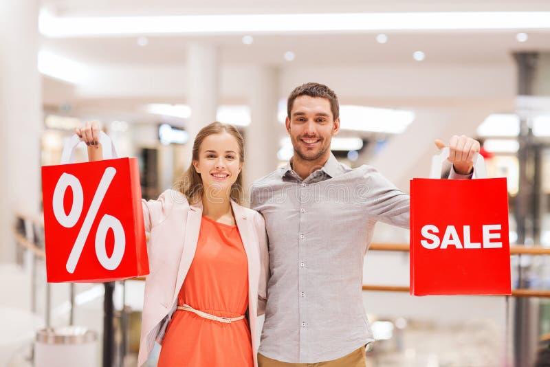 Szczęśliwi potomstwa dobierają się z czerwonymi torba na zakupy w centrum handlowym obrazy stock