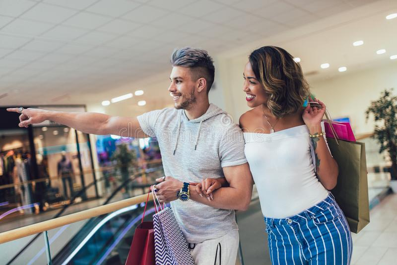 Szczęśliwi potomstwa dobierają się z torba na zakupy chodzi w centrum handlowym fotografia stock