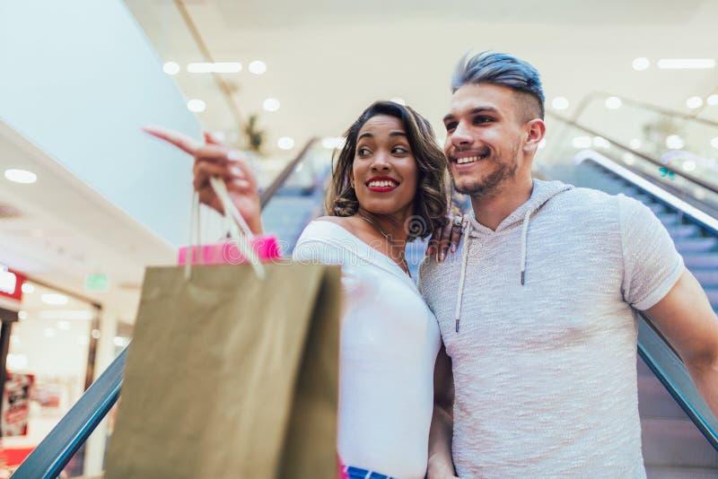 Szczęśliwi potomstwa dobierają się z torba na zakupy chodzi w centrum handlowym obrazy stock