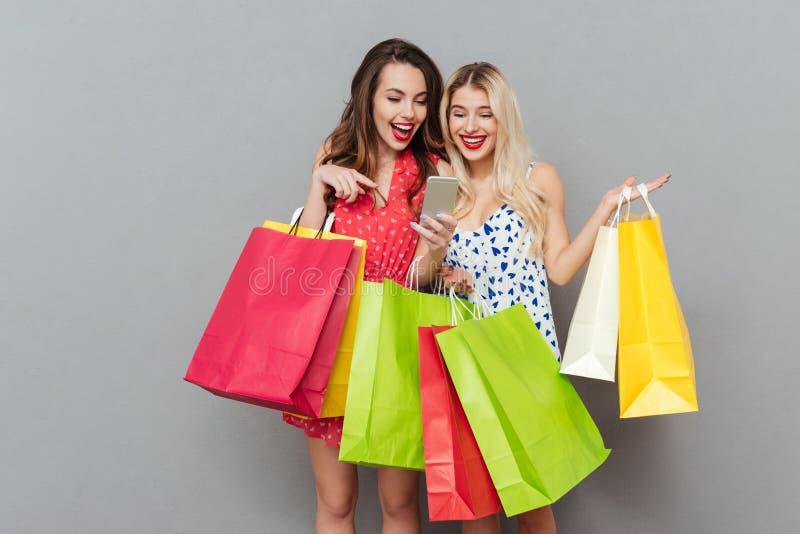 Szczęśliwi potomstwa dwa dama przyjaciela z torba na zakupy używać wiszącą ozdobę fotografia stock