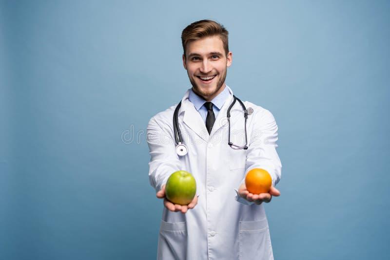 Szczęśliwi potomstwa fabrykują oferować wam pomarańcze i zieleni jabłka odizolowywających nad bławym obrazy stock