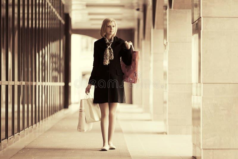 Szczęśliwi potomstwa fasonują kobiety z torba na zakupy przy centrum handlowego okno zdjęcie stock