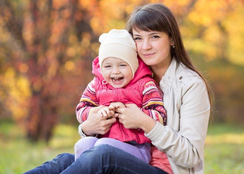 szczęśliwi potomstwa macierzyści i jej córki dziecko zabawę siedzieć przy spadkiem fotografia royalty free