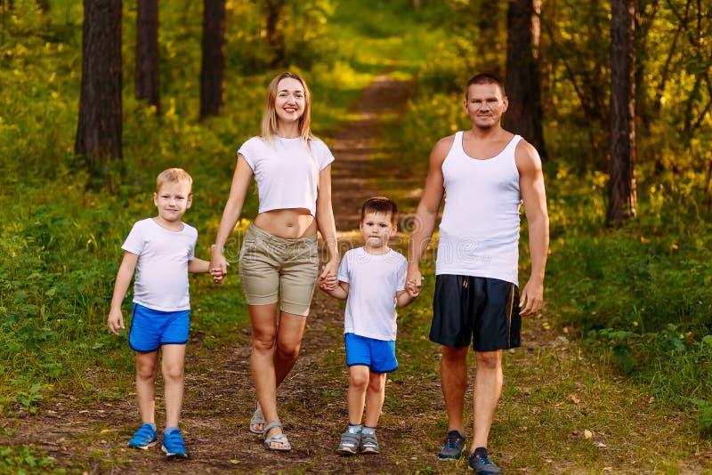 Szczęśliwi potomstwa matkują outdoors i ojcują i dwa dzieci lato Szczęśliwa rodzina chodzi przez drewien w białych koszulkach zdjęcie stock