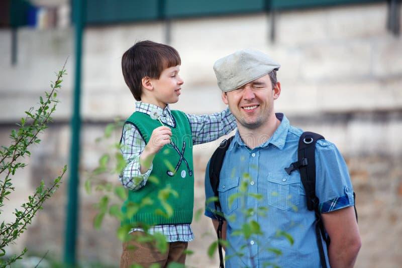 Szczęśliwi potomstwa ojcują outdoors i jego syn ma zabawę w mieście zdjęcie royalty free
