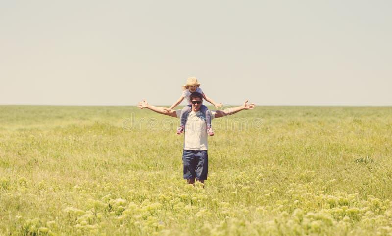 Szczęśliwi potomstwa ojcują trzymać jego małej córki na ramionach zdjęcia royalty free