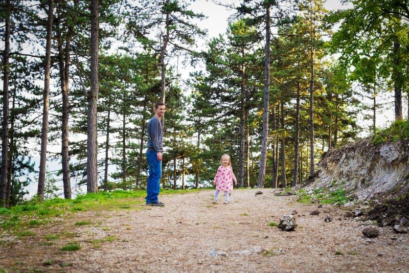 Szczęśliwi potomstwa przerzedżą ojca bierze spacer w parku z jego berbeć córką Rodzinny śmiać się zabawę i mieć fotografia stock