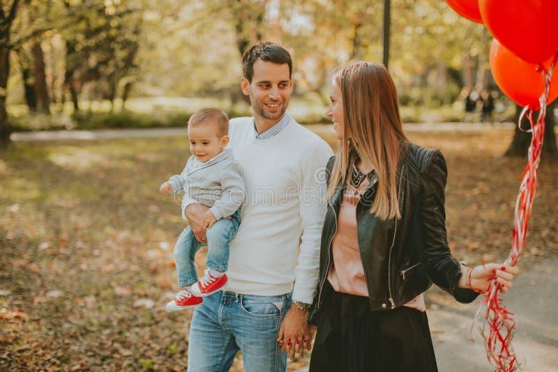 Szczęśliwi potomstwa wychowywają z chłopiec w jesień parku zdjęcia royalty free
