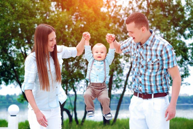 Szczęśliwi potomstwa wychowywają z mały syna bawić się plenerowy w parku fotografia royalty free