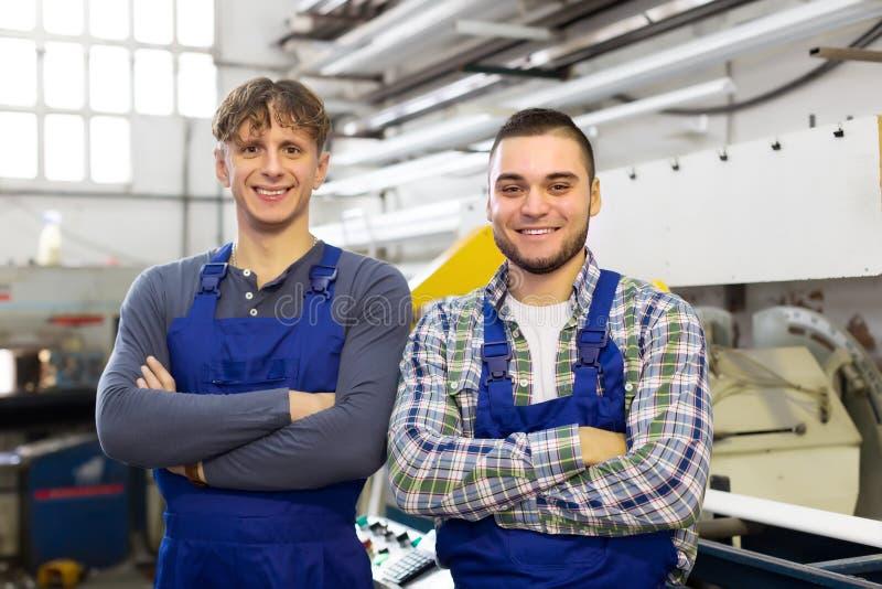 Szczęśliwi pracownicy przy nowożytną przemysł rośliną zdjęcia royalty free