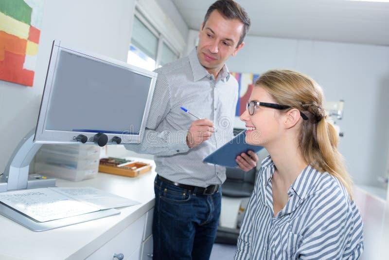 Szczęśliwi pracownicy siedzi laptop i patrzeje zdjęcie stock