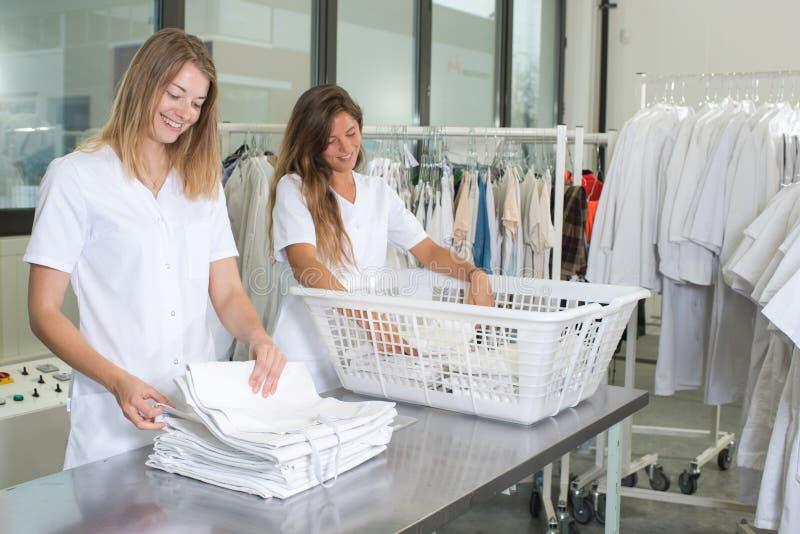 Szczęśliwi pralniani pracownicy przy suchymi czyścicielami fotografia royalty free