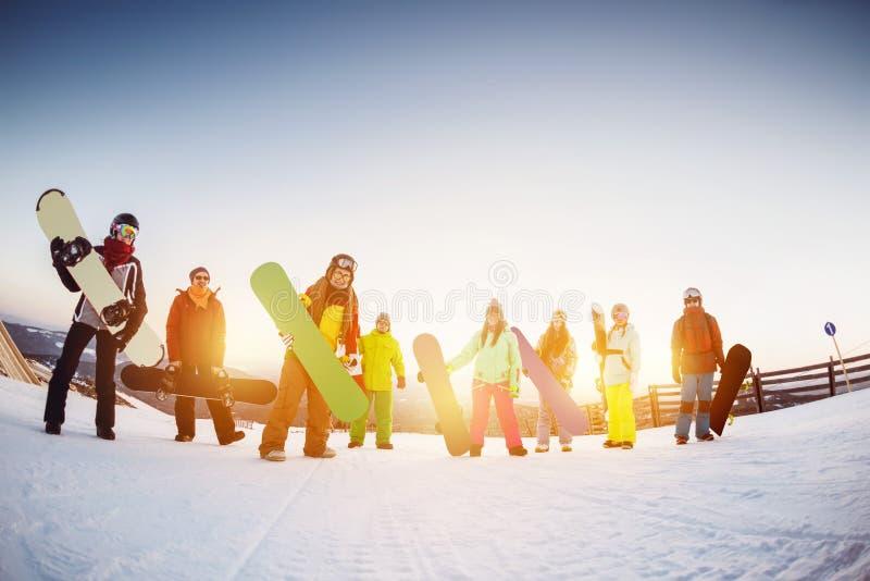 Szczęśliwi przyjaciół snowboarders przy ośrodkiem narciarskim obrazy stock