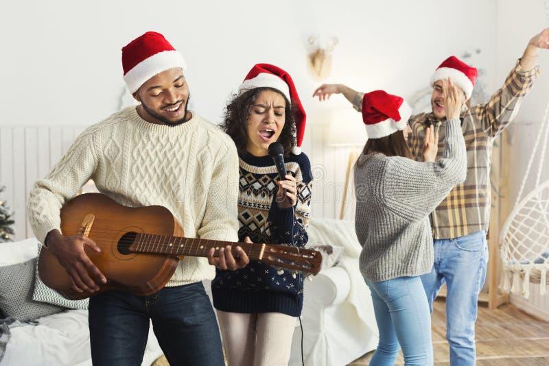 Szczęśliwi przyjaciele śpiewa wpólnie i bawić się na gitarze zdjęcie stock