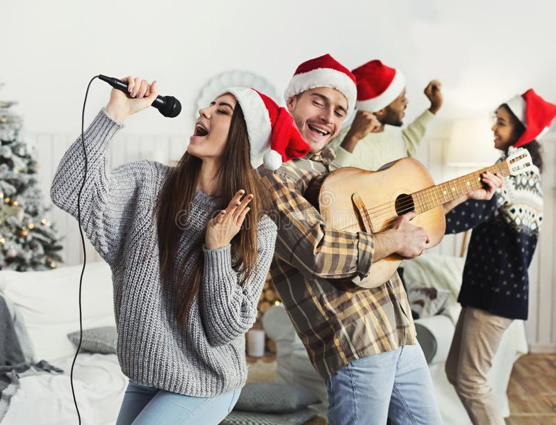 Szczęśliwi przyjaciele śpiewa wpólnie i bawić się na gitarze obrazy royalty free