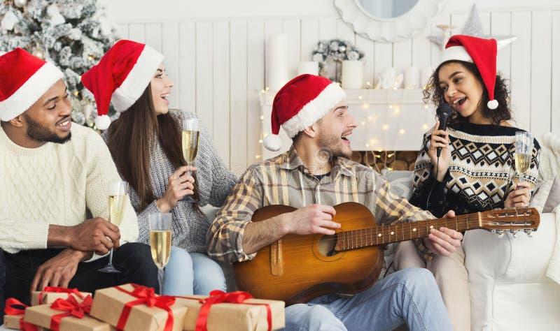 Szczęśliwi przyjaciele śpiewa wpólnie i bawić się na gitarze obrazy stock
