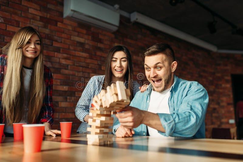 Szczęśliwi przyjaciele bawić się stołową grę przy stołem w kawiarni zdjęcia royalty free