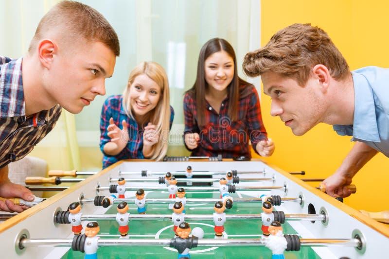 Szczęśliwi przyjaciele bawić się stołowego hokeja obraz stock