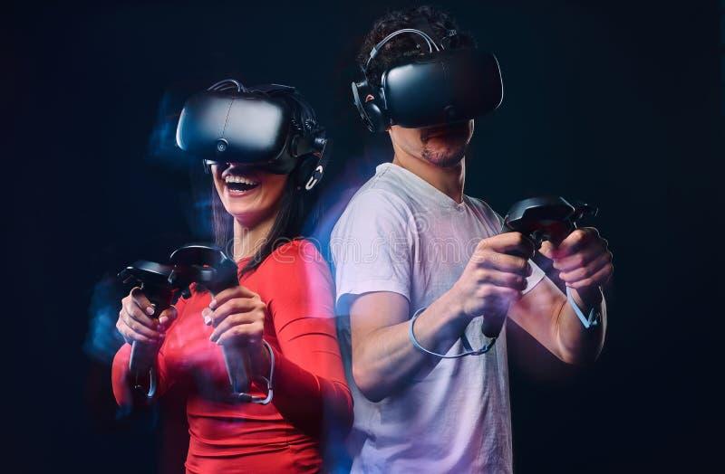 Szczęśliwi przyjaciele bawić się wideo gry jest ubranym rzeczywistość wirtualna szkła z kontrolerami Odizolowywający na ciemnym t zdjęcie royalty free