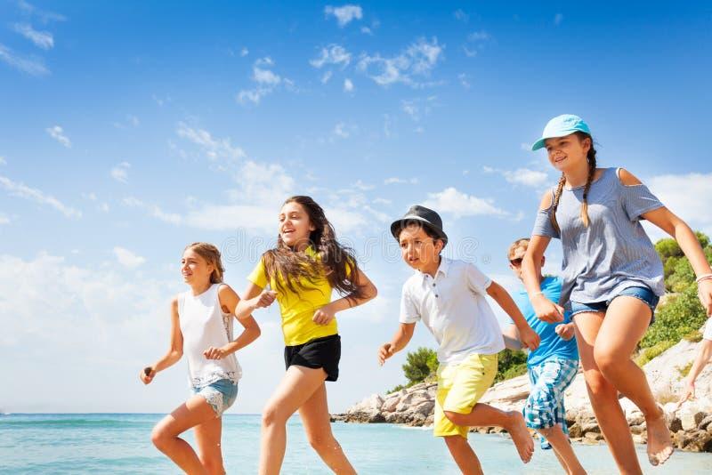 Szczęśliwi przyjaciele biega na lato plaży fotografia stock