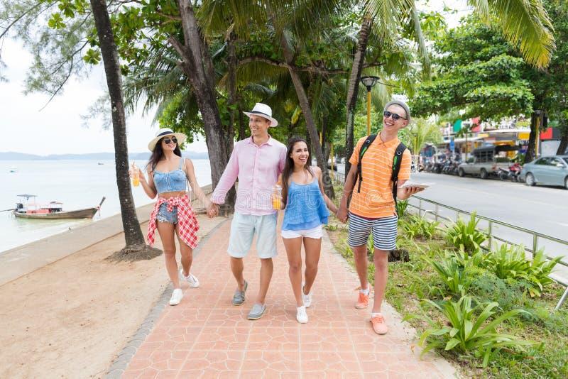 Szczęśliwi przyjaciele Chodzi Wpólnie W Parkowej Pobliskiej Dennej Młodej grupie ludzi Na Urlopowych turystach Wakacyjnych I Komu fotografia royalty free