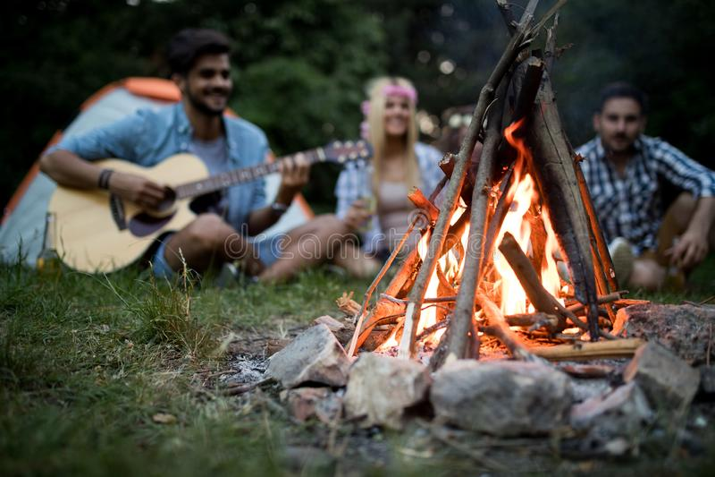 Szczęśliwi przyjaciele cieszy się muzycznego pobliskiego ognisko przy nocą zdjęcie stock