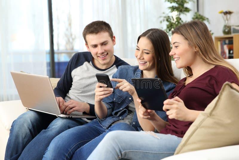 Szczęśliwi przyjaciele dzieli na linii zawartości w domu obraz stock