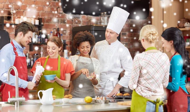 Szczęśliwi przyjaciele i szefa kuchni kucbarski kucharstwo w kuchni obrazy stock