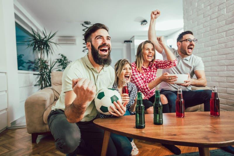 Szczęśliwi przyjaciele lub fan piłki nożnej ogląda piłkę nożną na tv obrazy royalty free