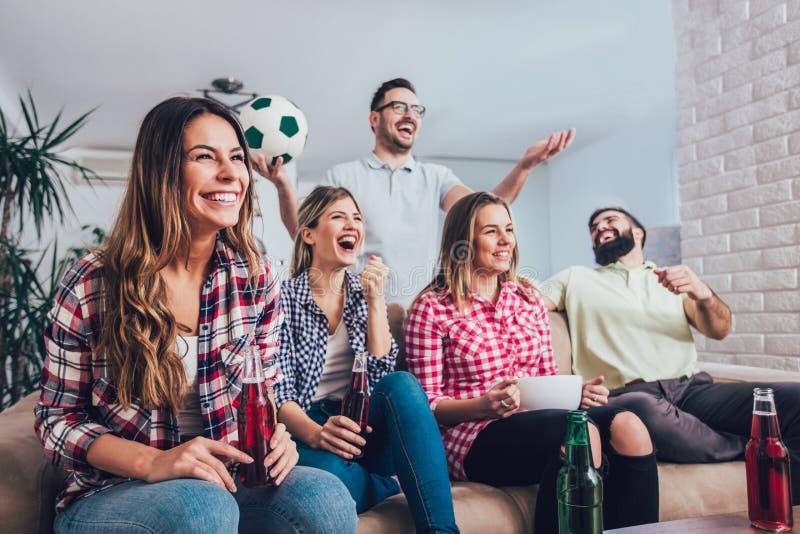 Szczęśliwi przyjaciele lub fan piłki nożnej ogląda piłkę nożną na tv zdjęcia stock