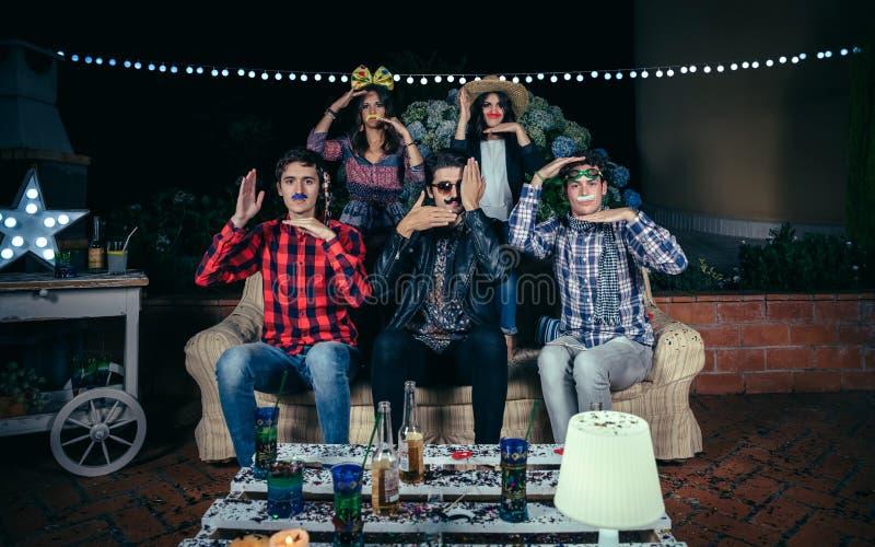 Szczęśliwi przyjaciele ma zabawę z kostiumami w przyjęciu zdjęcia stock