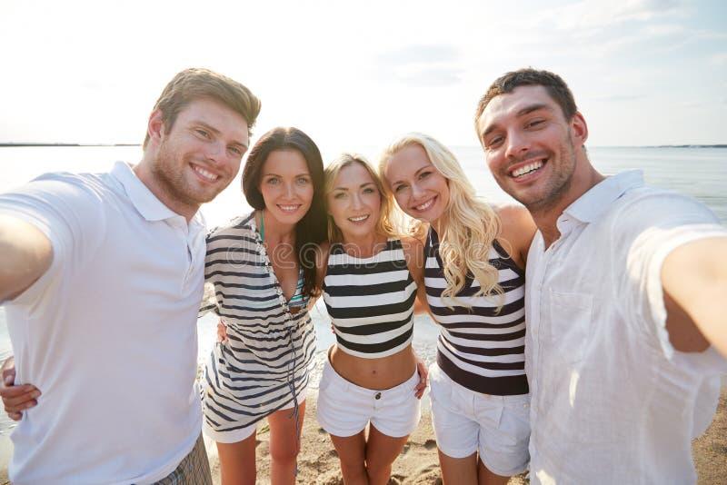 Szczęśliwi przyjaciele na plażowym i bierze selfie fotografia stock